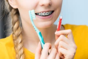 Dentist and orthodontist concept. Young woman smiling cleaning and brushing teeth with braces using toothbrush