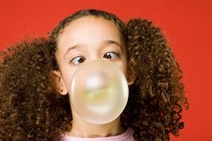 Little girl blows bubble gum bubble